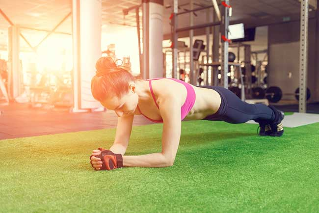 woman working her core and exercise her core and abs by doing the plank