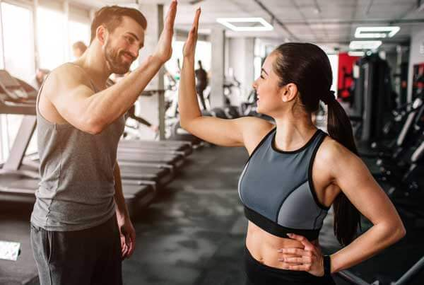 man and woman fit and healthy at the gym